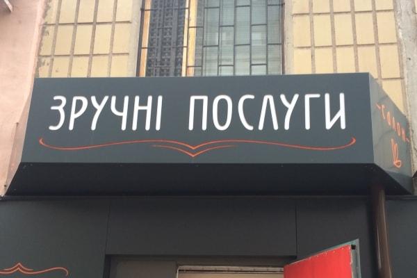 Рекламне оформлення входу - вивіска магазина послуг з літерами на проріз
