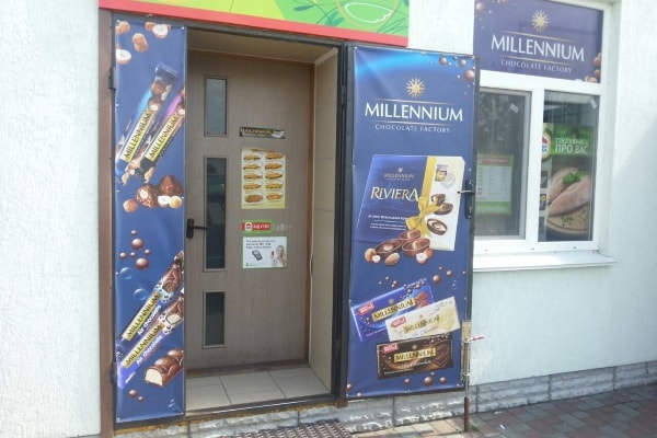 Оформление входных дверей продуктового магазина рекламными баннерами